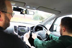 Driving instructor offering guidance in car